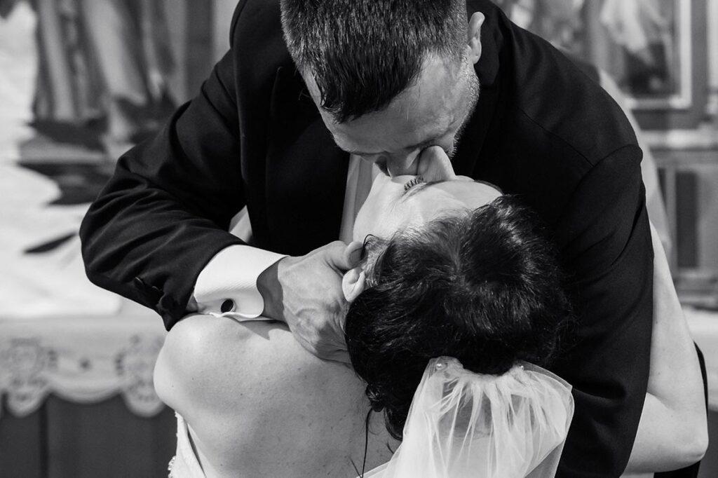 Brudgummen kysser bruden i kyrkan