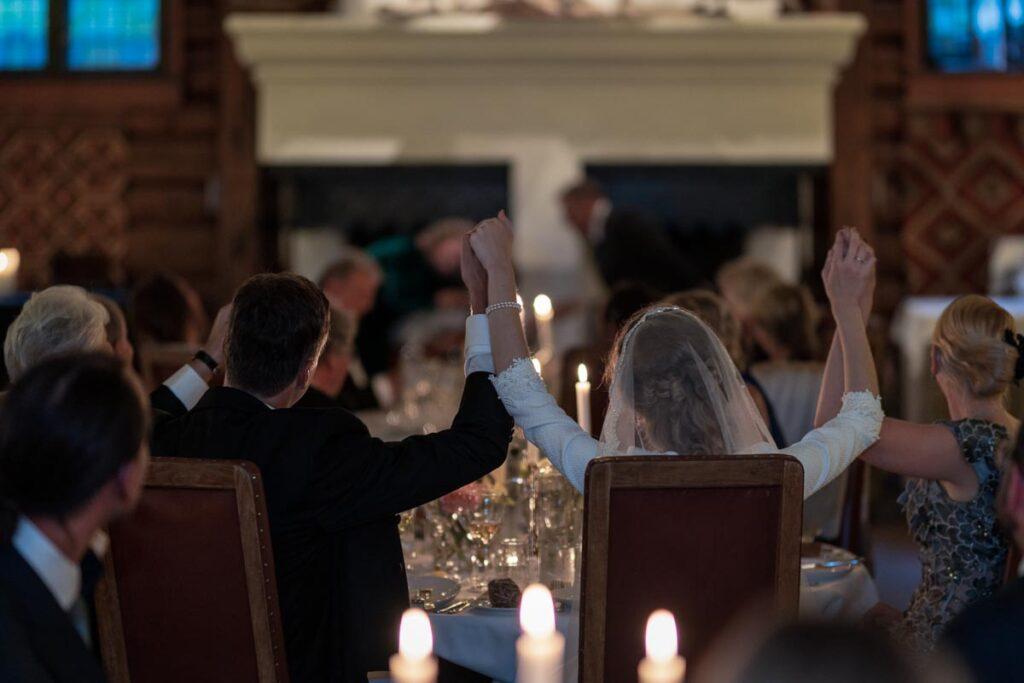 Bröllopspar håller händer med gäster under bröllopsfest