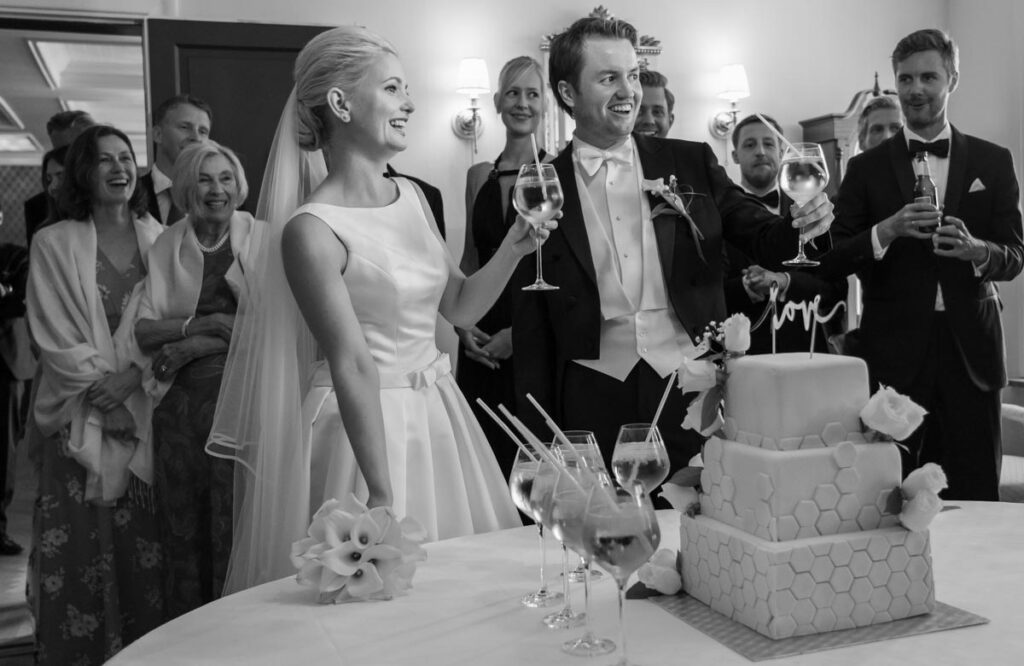 brudpar skålar med gäster framför bröllopstårta