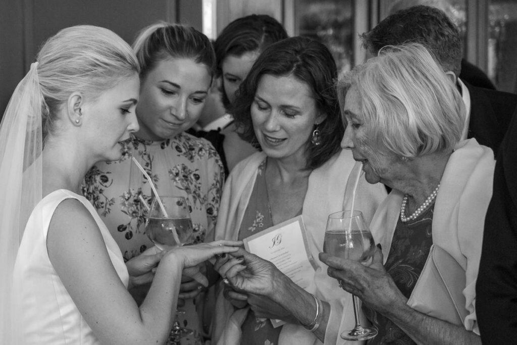 gäster beundrar brudens vigselring på bröllopsfest