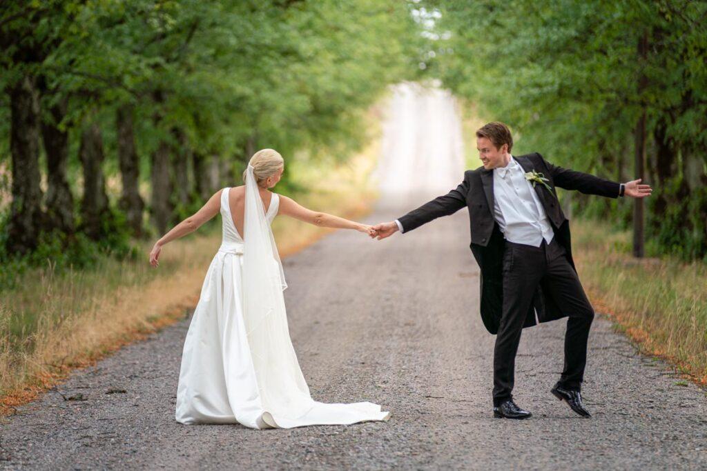 Bröllopspar dansar i en allé
