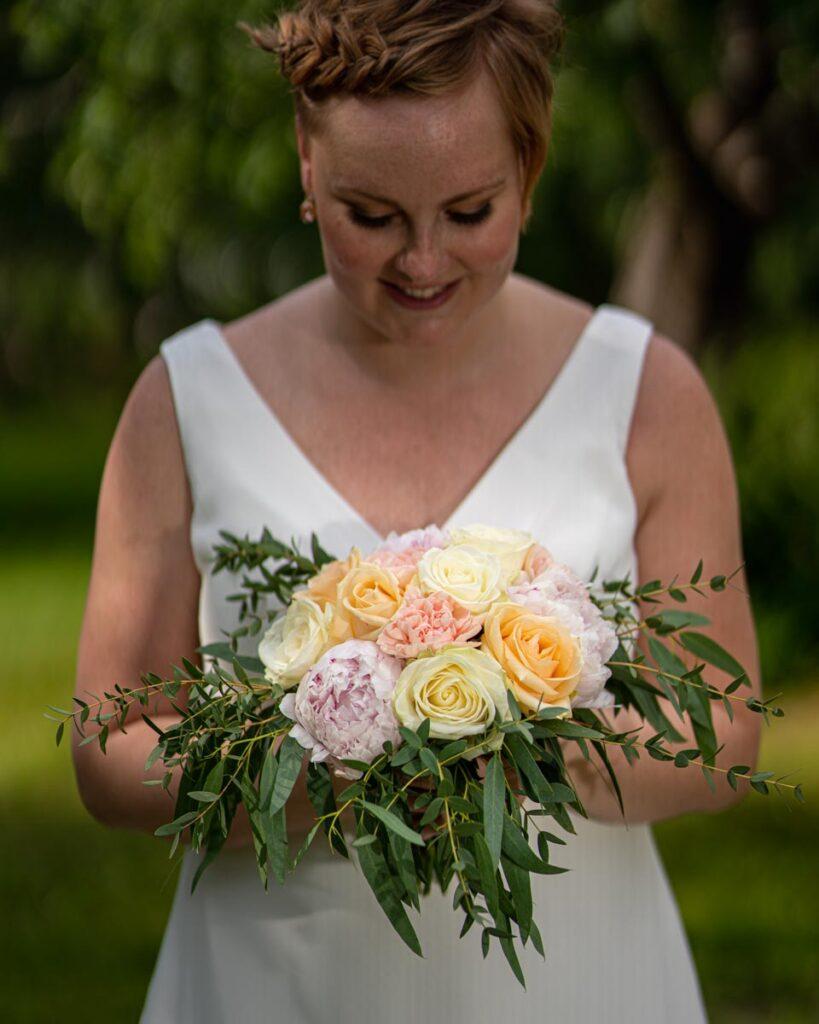 Brud poserar med bröllopsbukett på bröllopsdagen