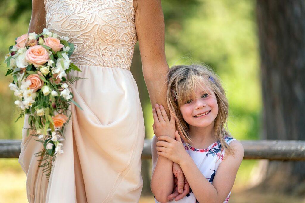 Liten flicka håller om nygift brud