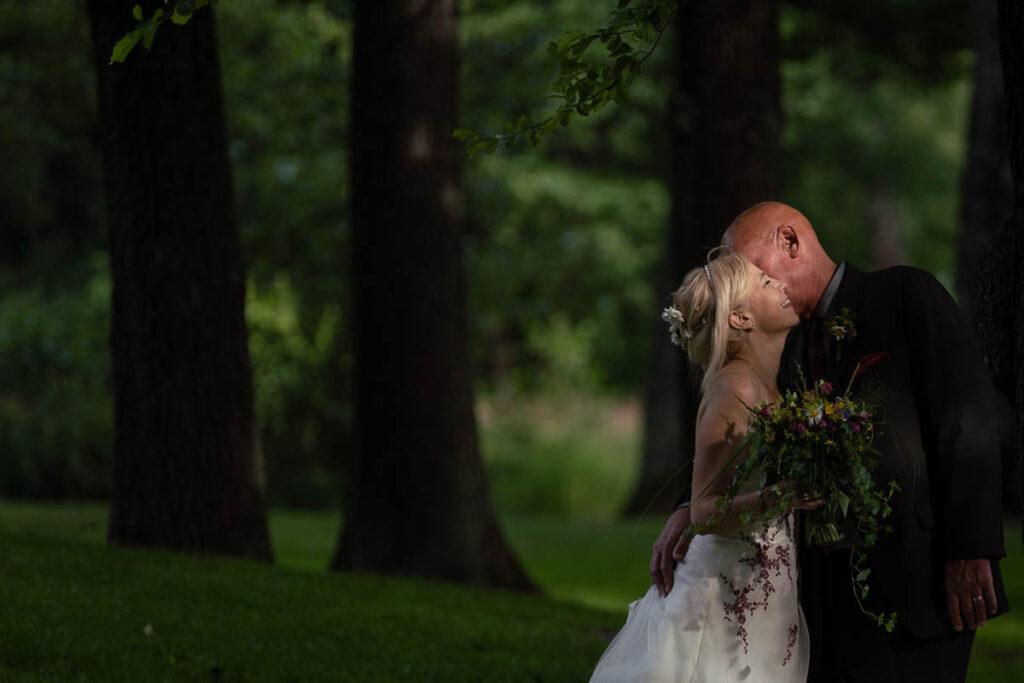 Bröllopspar kramas i skogen