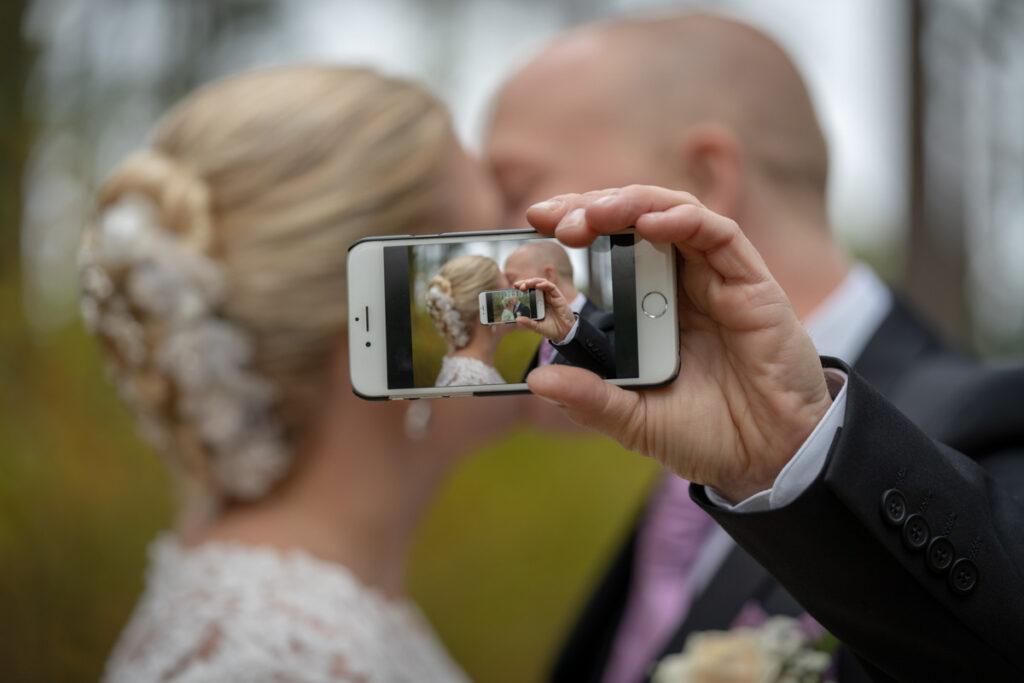 Bröllopspar kysser varandra bakom telefon