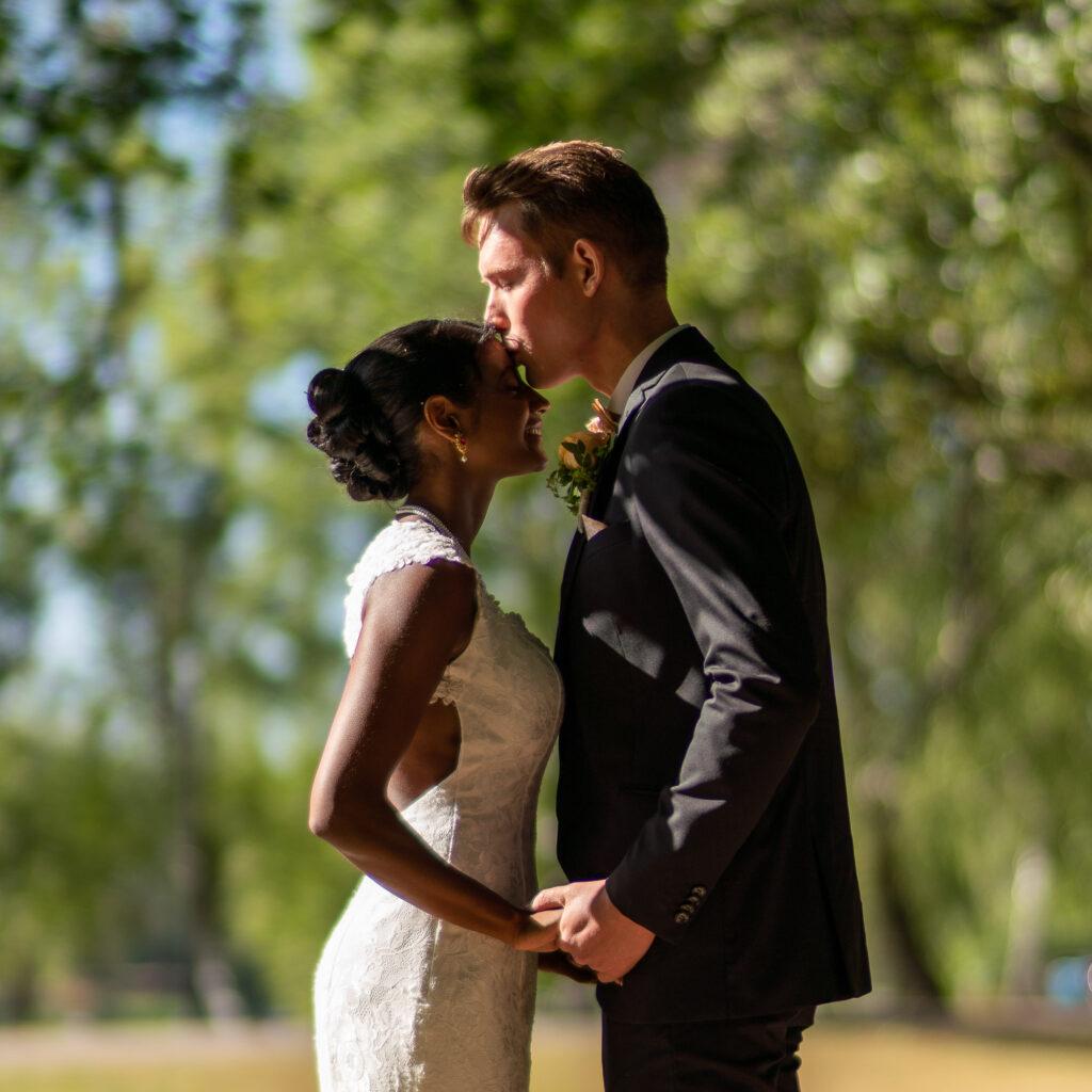 Brudgum kysser bruden på pannan i museiparken i Karlstad