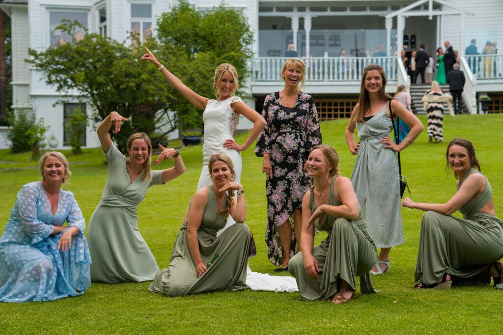 bruden poserar med brudtärnor och vänninor på gräsmattan framför hus