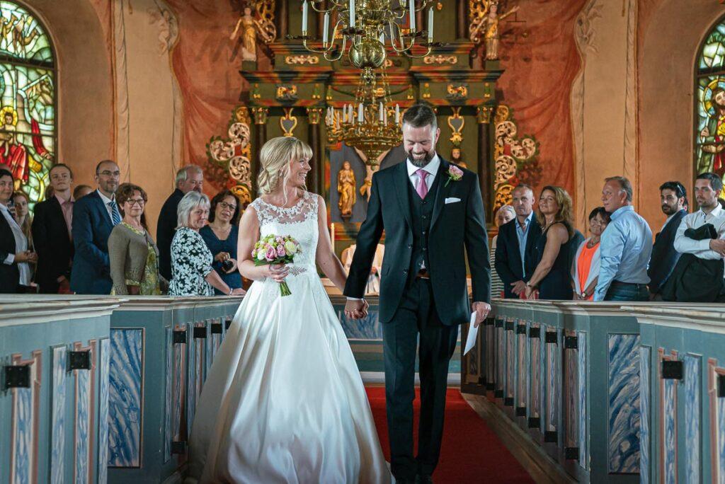 Nygift bröllopspar går hand i hand ut ur Gräsmark kyrka