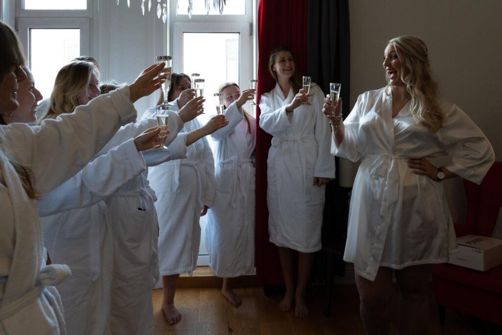 Bruden förbereder sig för bröllop och skålar med vänner och brudtärnor iförd morgonrock