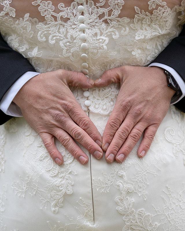 brudgum-gor-hjarta-med-hander-pa-brudens-rygg