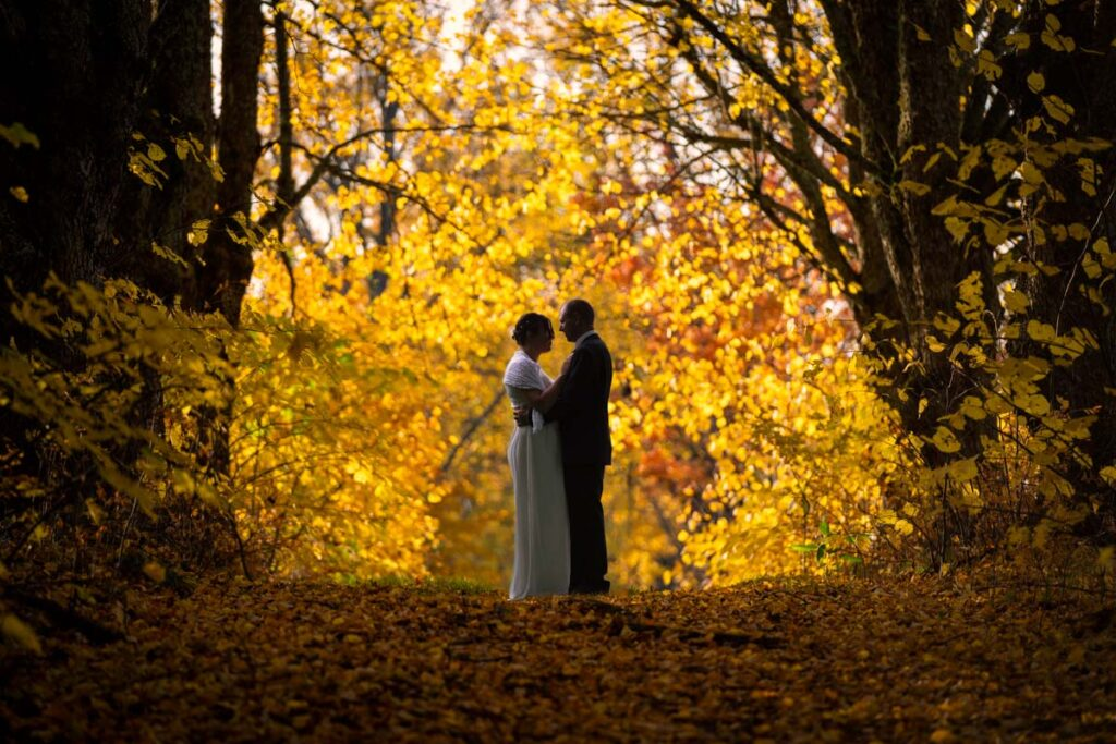 Bröllopspar står på en stig i höst skog