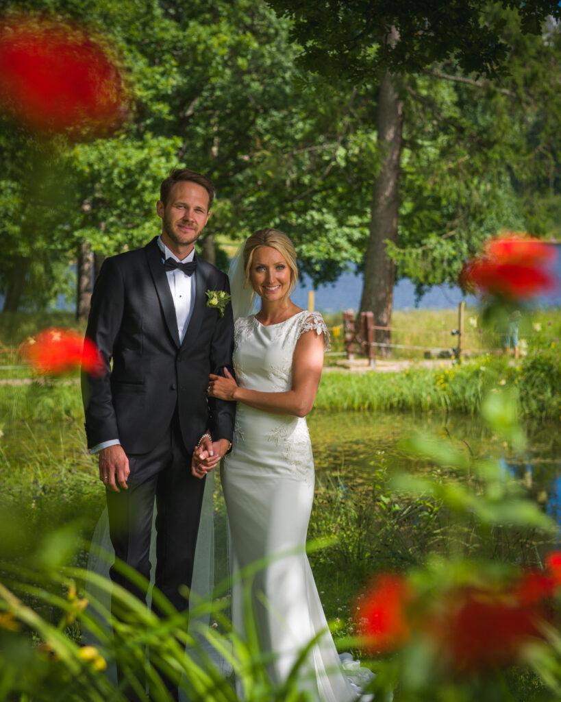 Brudpar poserar bland röda blommor