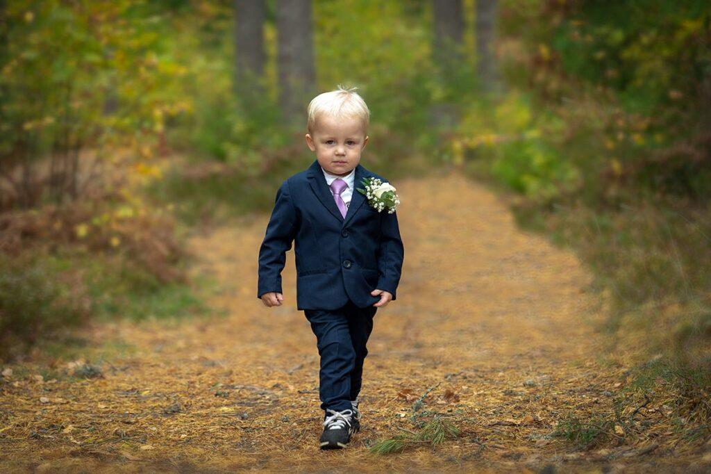 Liten pojke går på stig klädd i kostym