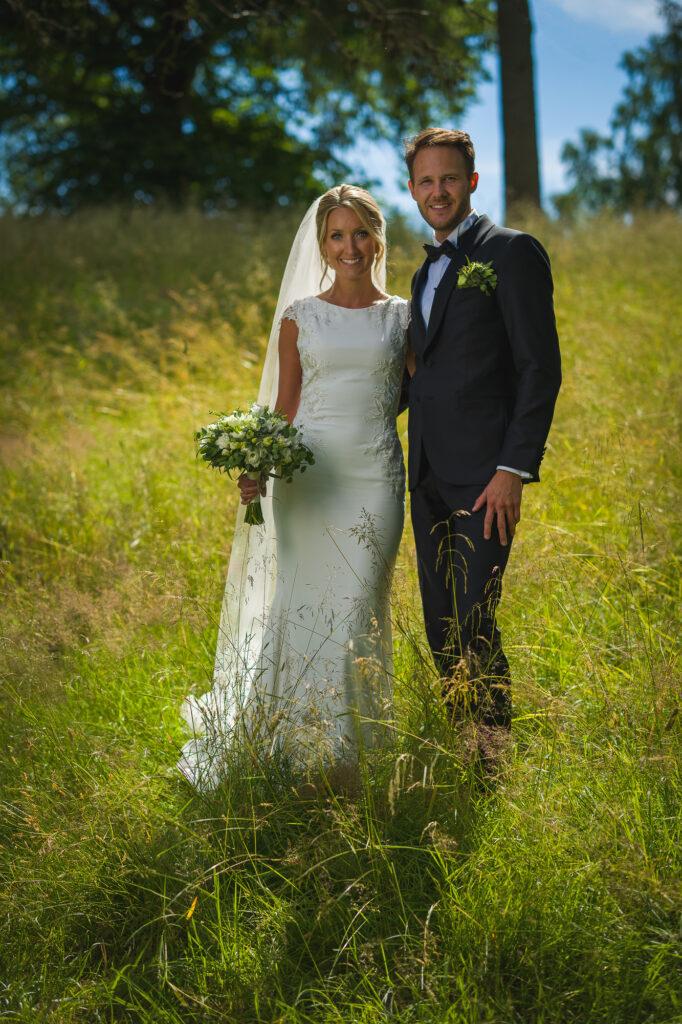 Brudpar poserar i högt gräs